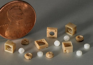 Micro molded components next to penny demonstrating micro molding capabilities.
