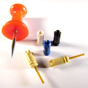 Micro molded PEEK parts, some with glass overmolding, next to a push pin to show scale.