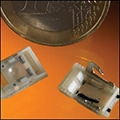 An example of high-speed reel-to-reel micro molding next to a Euro coin to show the small size.