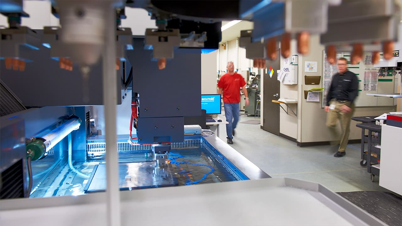 This image shows Accumold engineers walking through the company's cutting-edge tool room, equipped to produce the most sophisticated micro mold tooling.